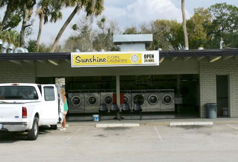 Okeechobee Parrot Avenue Location. Exterior and parking lot. Sign: Sunshine Coin Laundry.