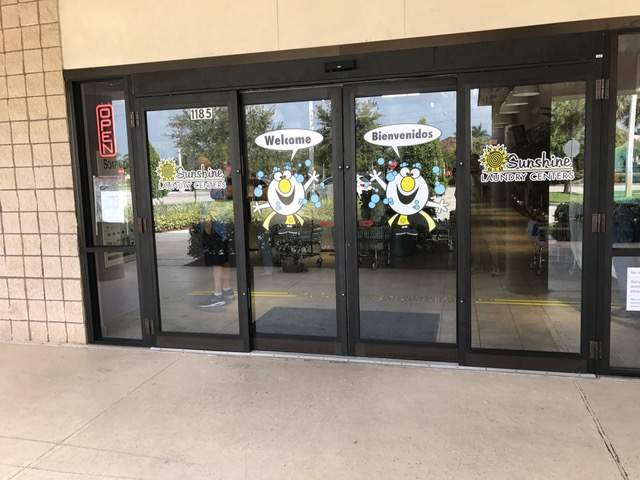 Clean exterior. Glass doors with Sunshine Laundry mascot image. Door reads Welcome and Bienvenidos.