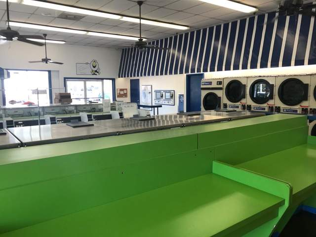 Washers and Dryer. Long table. Clean green counter. Ceiling fans.